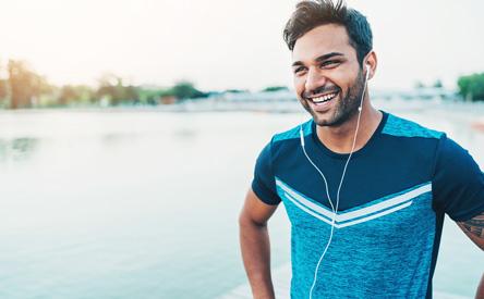 man smiling in front of lake