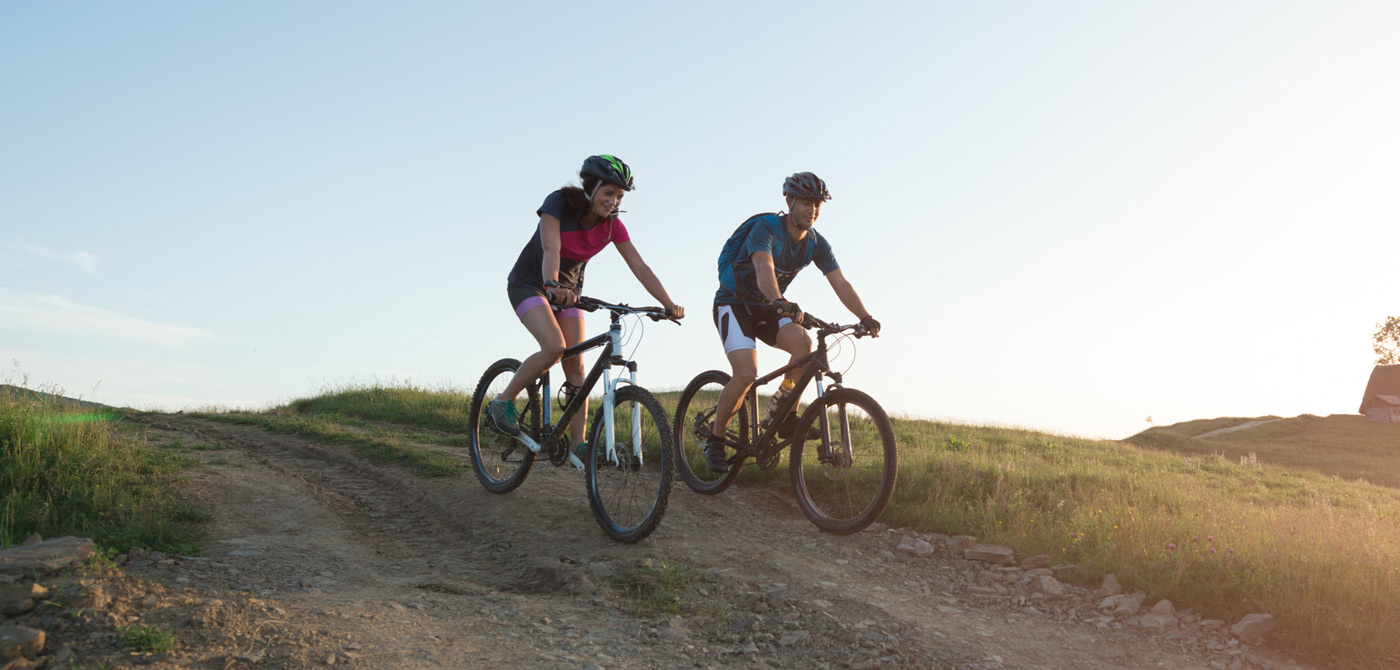 two bikers going down a dirt road