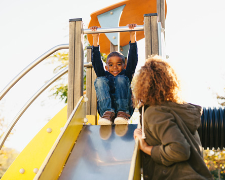young boy about to slide down a playground slide