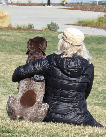woman hugging dog on grass