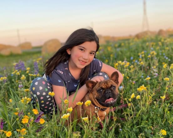 girl with dog in flower field