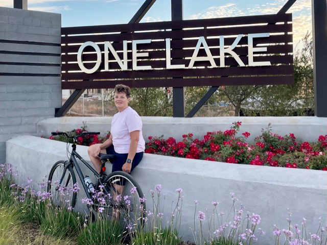dana crawford in front of one lake sign